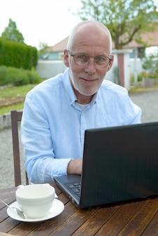 Старший мужчина, используя ноутбук за пределами