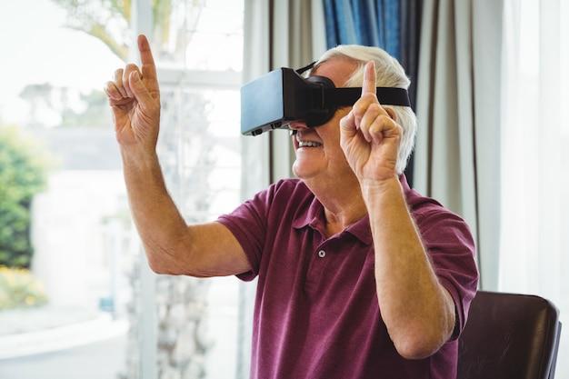 Старший мужчина с помощью устройства виртуальной реальности