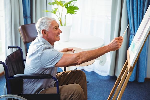 Senior man using brush and easel