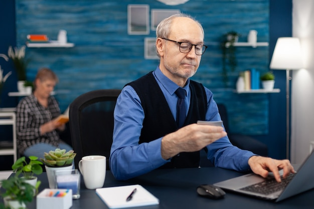 クレジットカードを使用して銀行口座を確認する年配の男性。妻がソファに座って本を読んでいる間、ラップトップを見てshppping支払いをするためにオンラインバンキングをチェックしている老人。