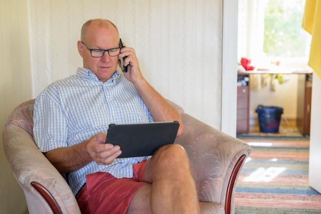 自宅でデジタルタブレットと電話を使用して年配の男性