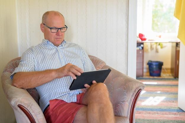 居間でデジタルタブレットを使用して年配の男性