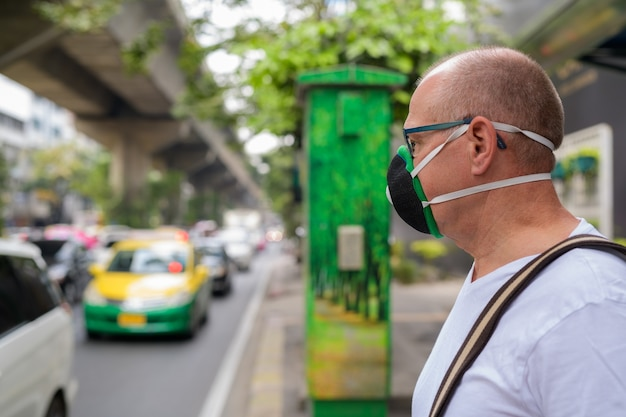 Senior man using face mask to protect from pollution smog