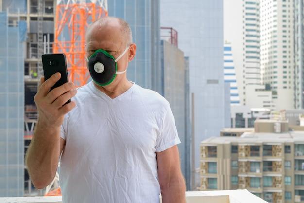 都市の汚染スモッグから保護するためにフェイスマスクを使用している年配の男性