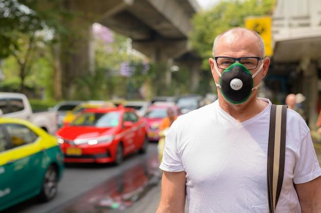오염 스모그로부터 보호하기 위해 얼굴 마스크를 사용하는 수석 남자