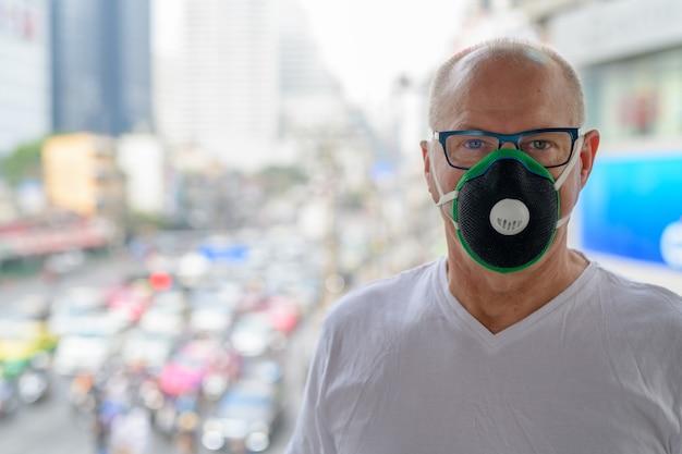 Старший мужчина использует маску для защиты от смога загрязнения