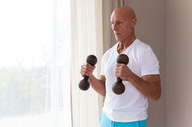 Senior man using fitness dumbbells
