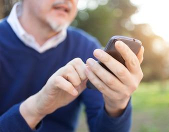 屋外で彼の携帯電話を使用している高齢者