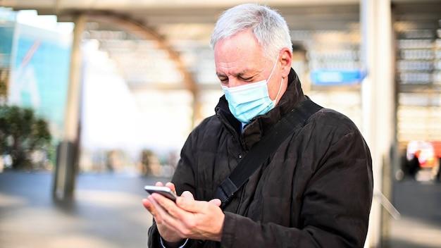 コロナウイルスのパンデミックから保護するためにマスクを着用しながら屋外でスマートフォンを使用している年配の男性