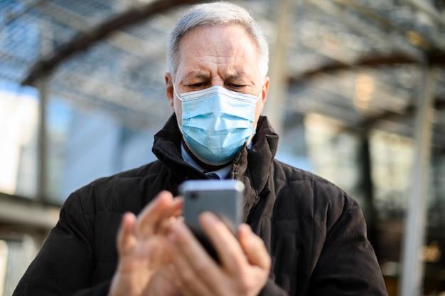 코로나 바이러스 전염병으로부터 보호하기 위해 마스크를 쓰고 야외에서 스마트 폰을 사용하는 시니어 남자