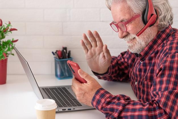 Старший мужчина дома с помощью портативного компьютера и мобильного телефона бизнесмен, работающий в офисе
