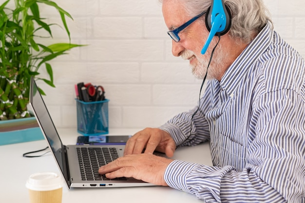 Senior man using laptop computer and mobile phone at home, businessman working in office.freelance, studying, technology online shopping