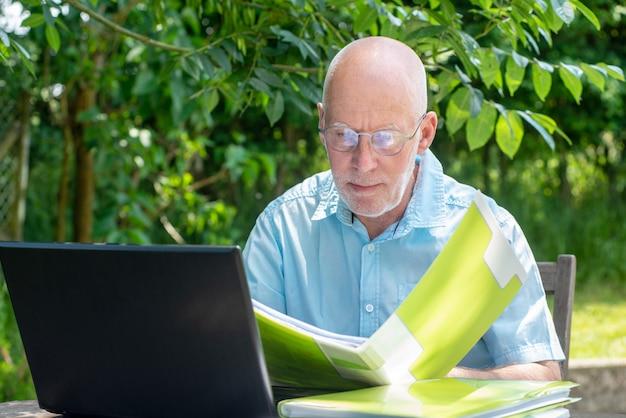 Старший мужчина, используя ноутбук в саду