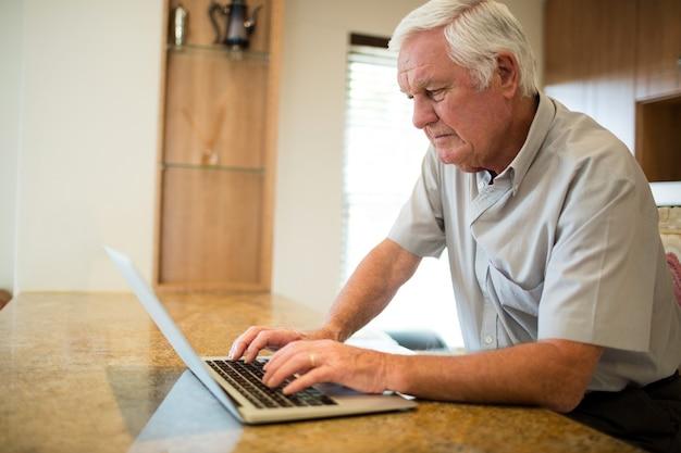 Старший мужчина, использующий ноутбук на кухне дома