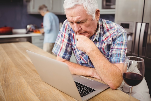Senior man using laptop and woman working in kitchen at home