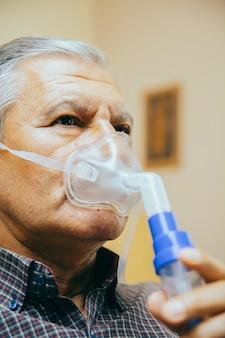 호흡기 마스크, 분무기 흡입을 위해 의료 기기를 사용하는 시니어 남자