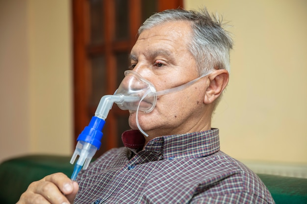 Senior man using medical equipment for inhalation with respiratory mask, nebulizer