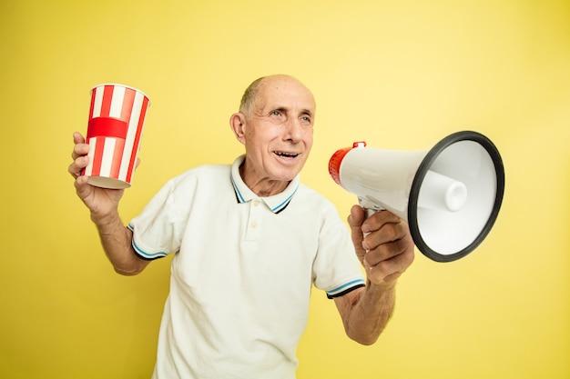 Старший мужчина использует мегафон и держит полосатый пакет