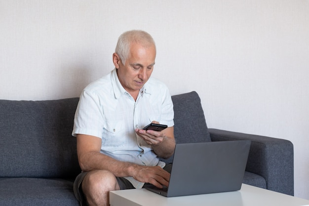 Senior man using mobile phone while working on computer in home office