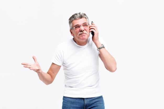 Старший мужчина, использующий смартфон, в стрессе, шокирован стыда и удивлен лицом, сердит и разочарован