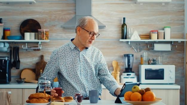 キッチンで朝食時にお茶を飲みながらタブレットコンピューターを使用している年配の男性。モバイルアプリ、現代のインターネットオンライン情報技術を使用して定年のタブレットポータブルパッドpcを持つ高齢者