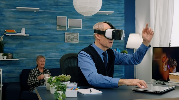 Senior man using virtual reality goggles in living room gesturing