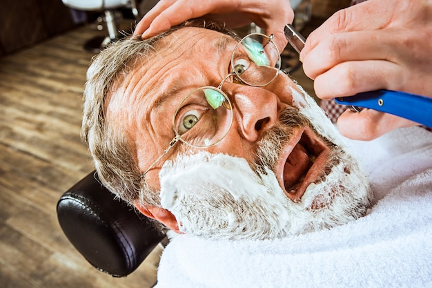 Senior man visiting hairstylist in barber shop.