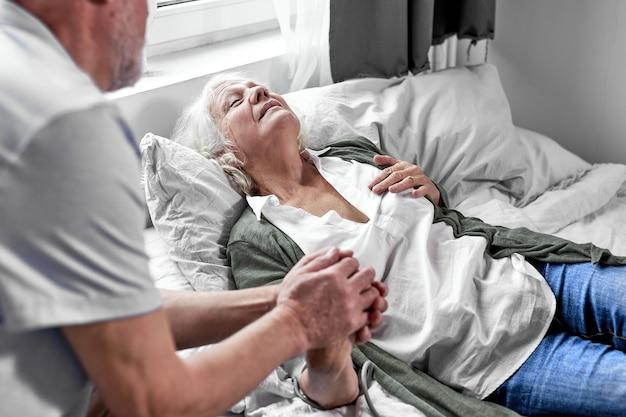 病棟で病人妻を訪ねる年配の男性、サポートと支援。健康、医学の概念