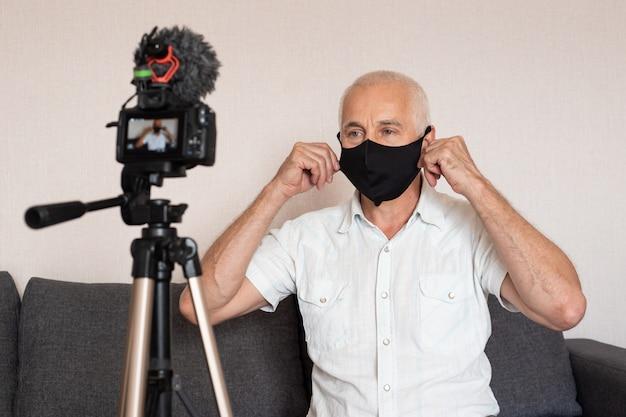 年配の男性のvloggerがビデオブログを記録しています。三脚に取り付けられたカメラを使用してビデオを記録するブロガー