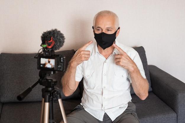 年配の男性のvloggerがビデオブログを記録しています。三脚に取り付けられたカメラを使用してビデオを記録するvlogger