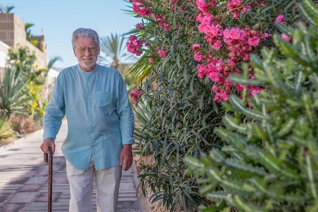 나무 막대기의 도움으로 야외에서 산책 하는 수석 남자. 꽃이 만발한 정원