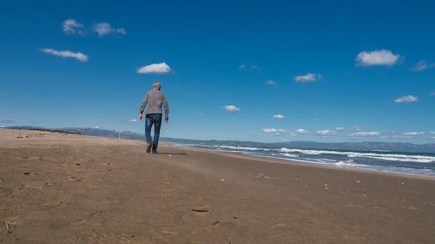 겨울 자연 해변 개념에 해변을 걷는 수석 남자