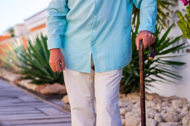 Senior man walking in outdoor with the help of a wooden stick. garden in background