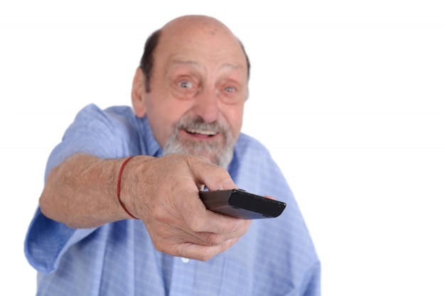 Senior man watching tv with remote control