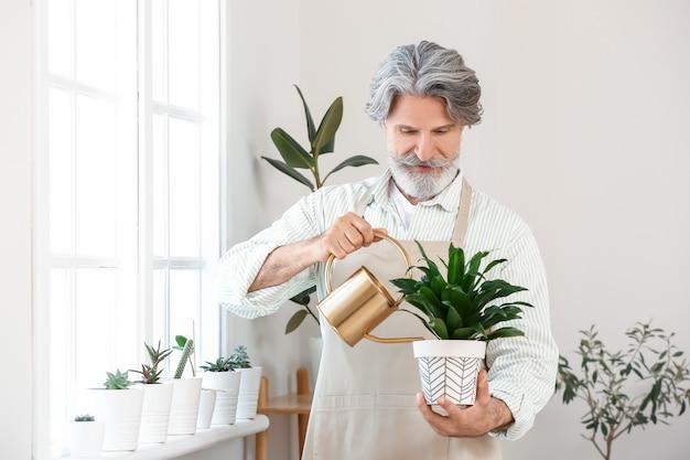 Старший мужчина поливает растения дома