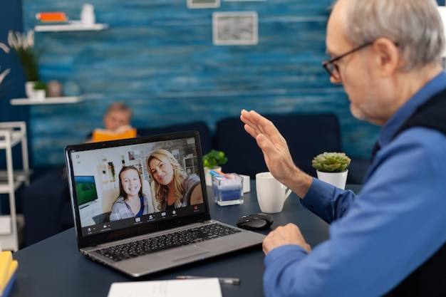 Senior man waving at daughter and niece during video conference