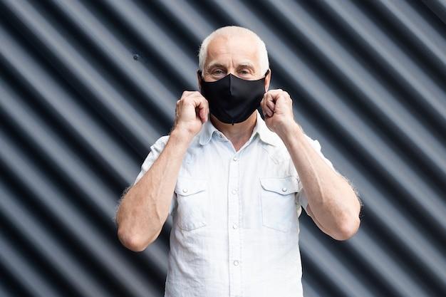 그의 얼굴을 만지고 보호 의료 마스크를 쓰고 수석 남자