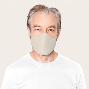 Старший мужчина в бежевой маске для лица кампания covid-19 с дизайнерским пространством