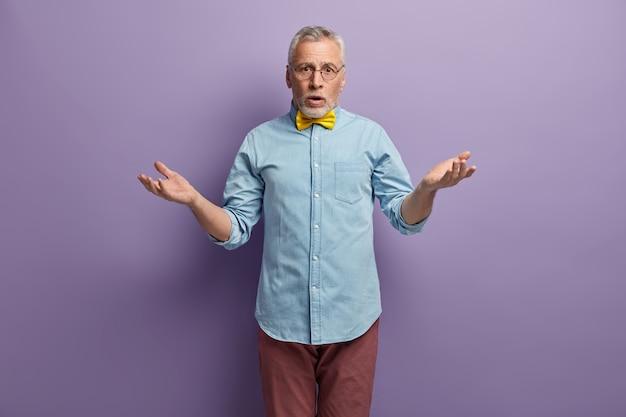 Старший мужчина в синей рубашке и желтом галстуке-бабочке