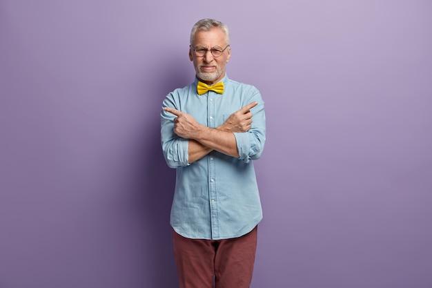 Uomo maggiore che indossa camicia blu e papillon giallo