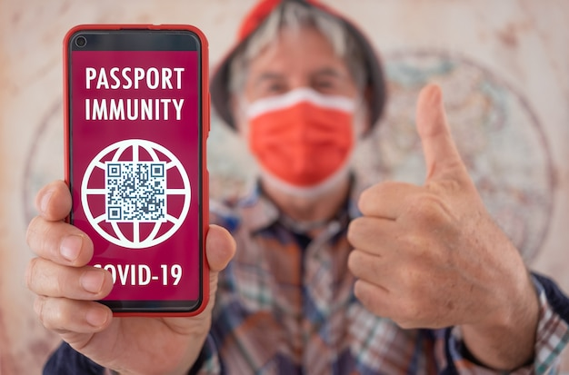 Senior man wearing face mask shows health passport app for people vaccinated against coronavirus