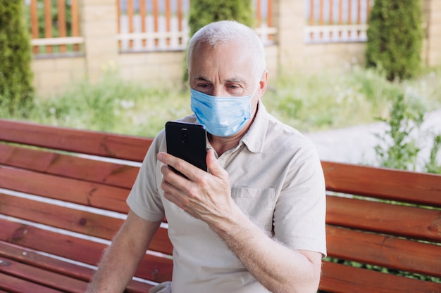 Senior man wearing protective mask using smartphone