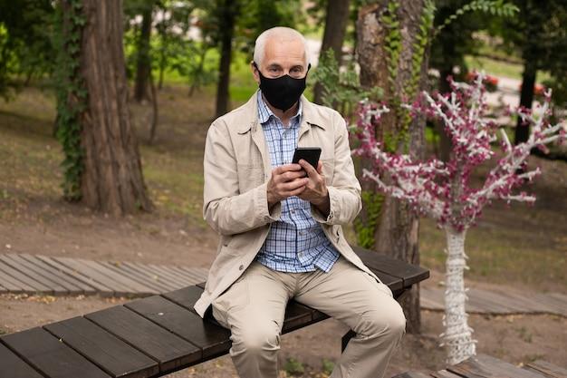 공원에서 스마트 폰을 사용하는 동안 보호 마스크를 쓰고 수석 남자