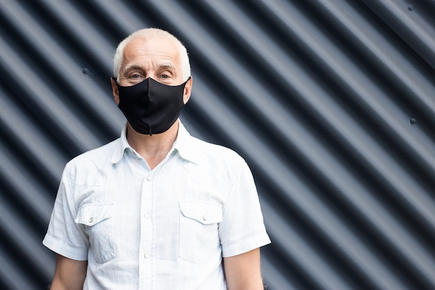 Senior man wearing a protective medical mask, place for text, copyspace