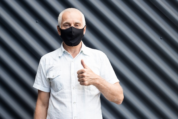 Senior man wearing a protective medical mask showing thumbs up gesture, place for text, copyspace