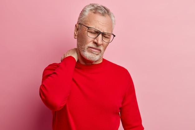 Старший мужчина в красном свитере и модных очках