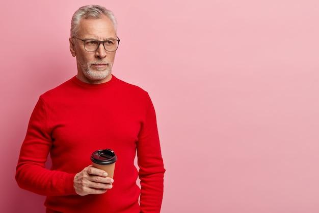 赤いセーターと流行の眼鏡をかけている年配の男性