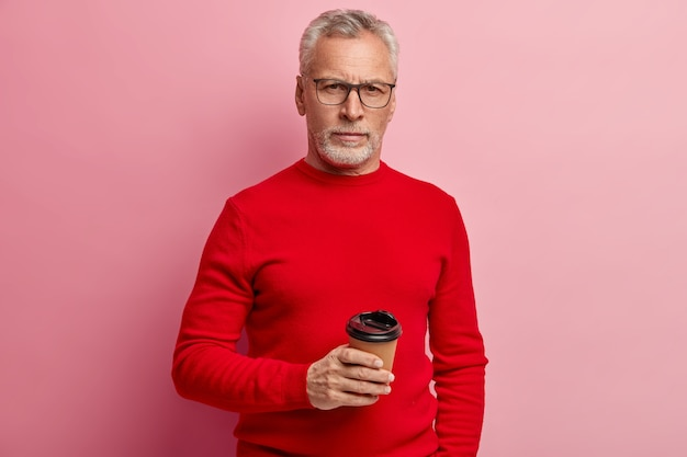 Senior man wearing red sweater and trendy eyeglasses