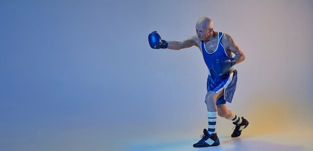 Senior man wearing sportwear boxing isolated on gradient studio wall