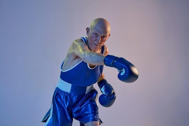Старший мужчина в спортивной одежде боксирует на стене студии градиента